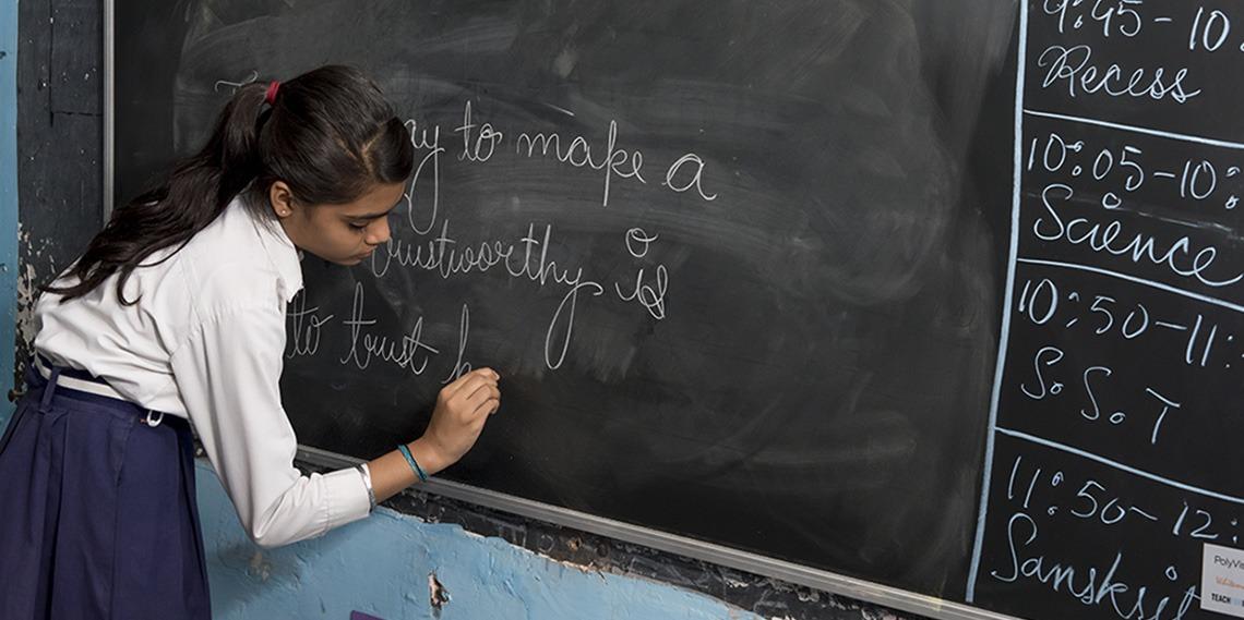 Een meisje in India dat schrijft op PolyVision's interactive e3 CeramicSteel-krijtbordoppervlakken