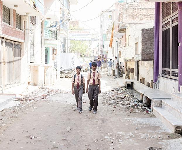 Twee jongens in schoolkleding en met rugzak lopend op weg naar school in India