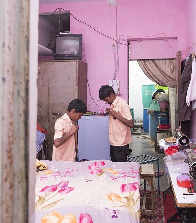 Twee jongens die hun schooloverhemd dichtknopen in een roze ruimte