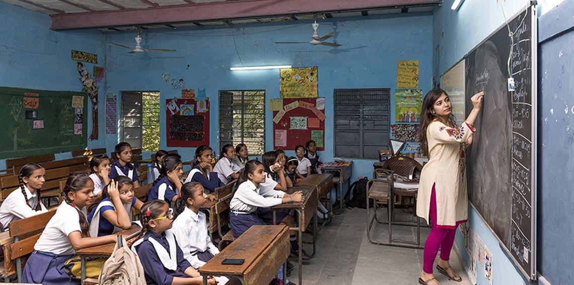 Schoolomgeving in India met leerlingen die kijken naar hun onderwijzer die schrijft op e3 CeramicSteel-materialen in de klas