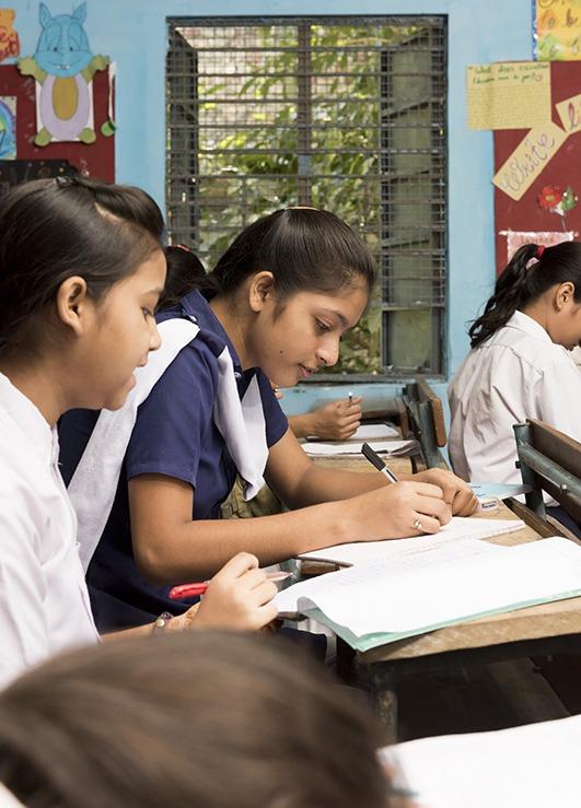 Leerlingen die in hun schrift schrijven aan bureautjes in een Indiase school
