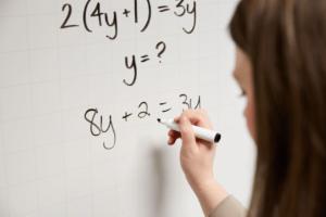 Woman writing algebraic equation on whiteboard in black marker