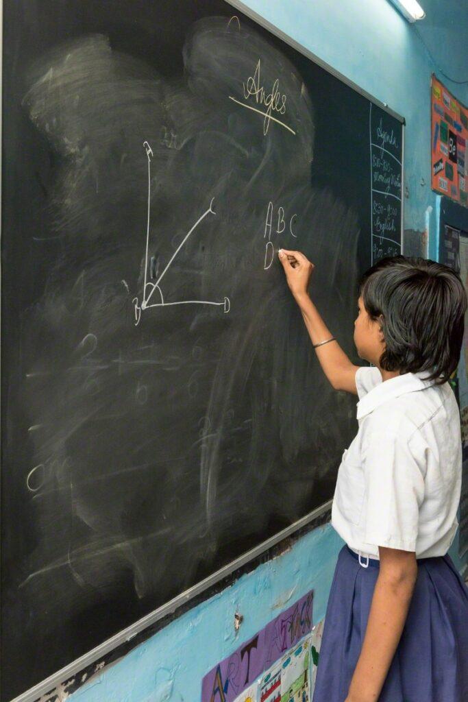 Niños dibujando ángulos geométricos sobre un pizarrón