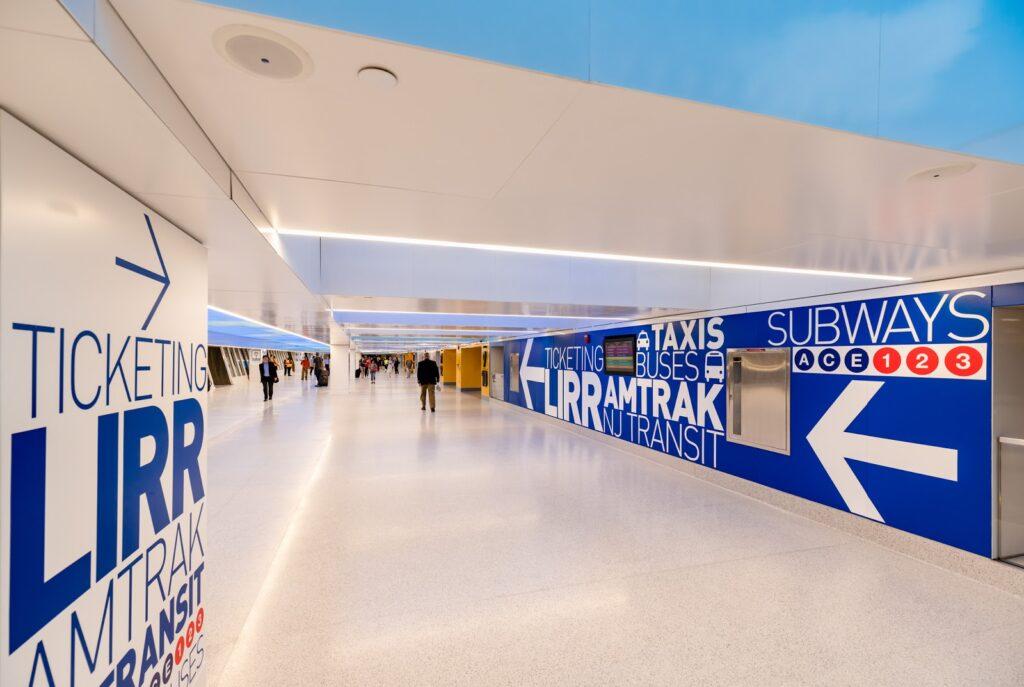 Station de métro avec des murs bleus et de grands mots avec des directions