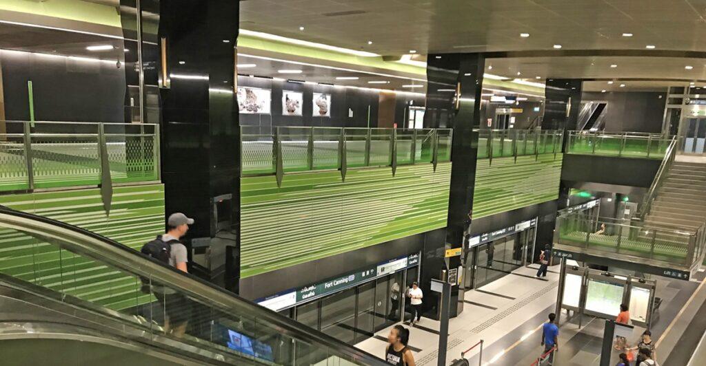 Felgroene panelen aan de muren van een metrostation en mensen die er doorheen lopen