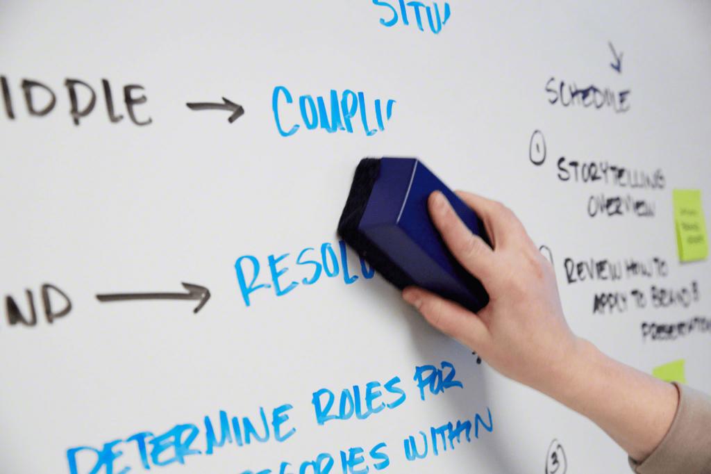 Eine Hand, die einen blauen Löscherhält und Markertinte und Notizen von einem trocken abwischbaren Board entfernt