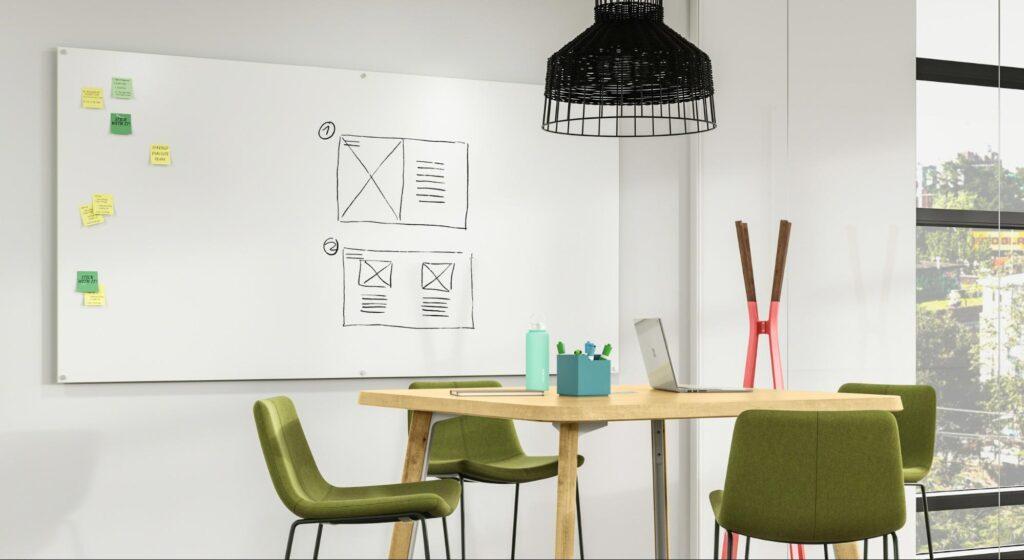 大型办公室白板挂在配有绿色椅子和吊顶灯的木桌旁的墙壁上