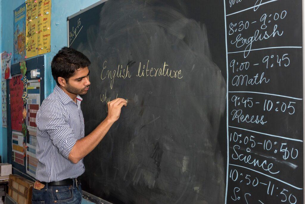 Professor escreve no quadro-negro com giz na sala de aula