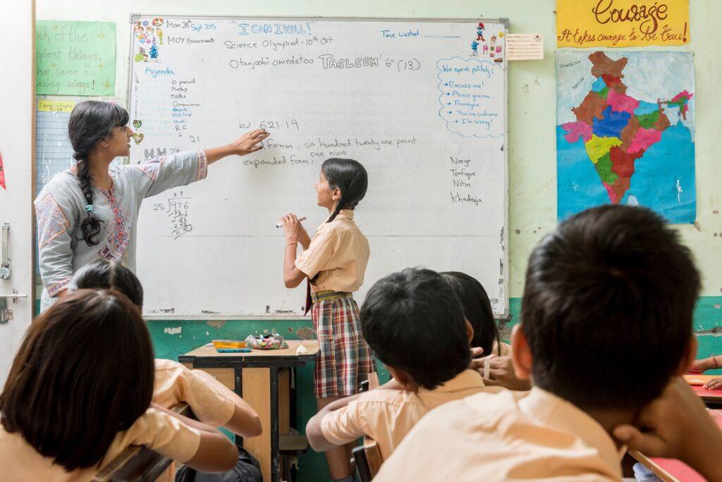 Professora aponta para a escrita nowhiteboard na frente dos alunos