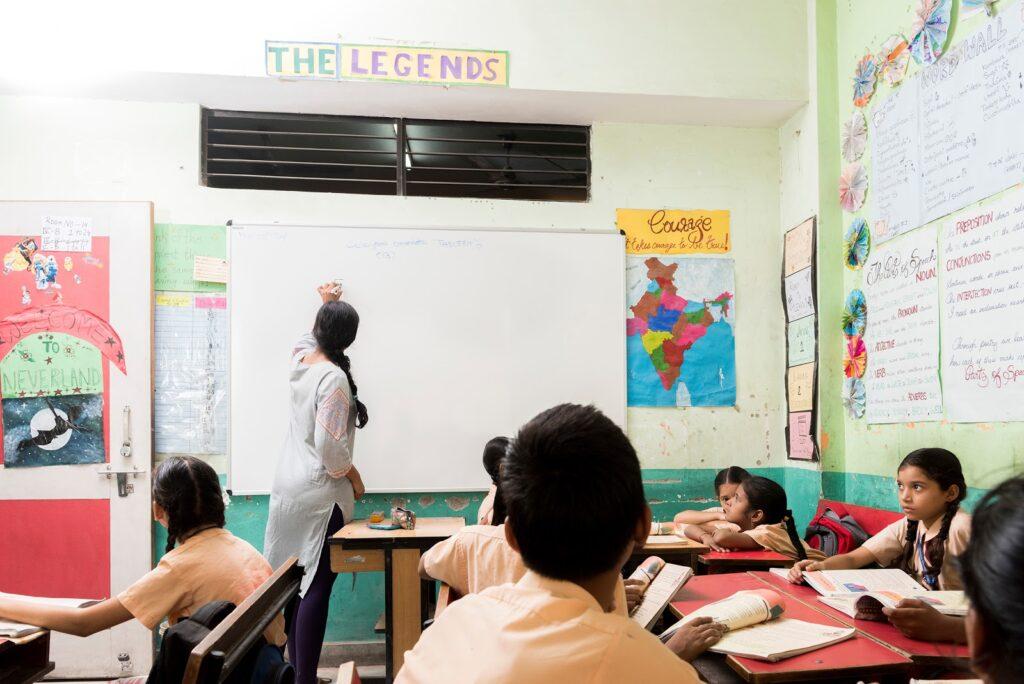 Professora escreve nowhiteboard na frente da sala de aula dos alunos