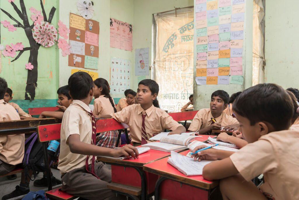 Alunos em sala de aula na Índia sentados em carteiras agrupadas