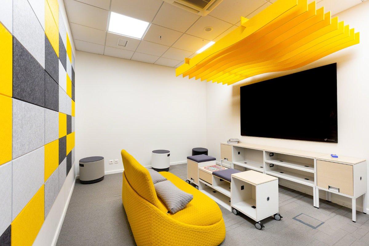 Bureau avec meubles jaunes, armoire blanche et écran sur le mur