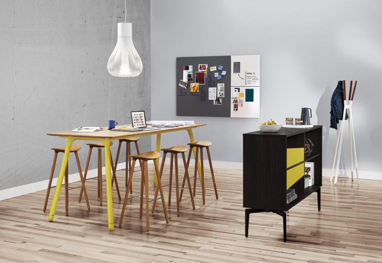 Área de colaboración de oficina con biblioteca negra, mesa de reuniones larga, taburetes de madera y pizarra blanca montada en la pared