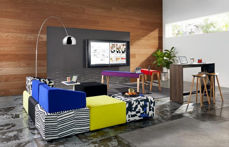 Sofá seccional multicolor en el interior de la sala de estar de la oficina con asientos de banco, mesitas y monitor montado en la pared.
