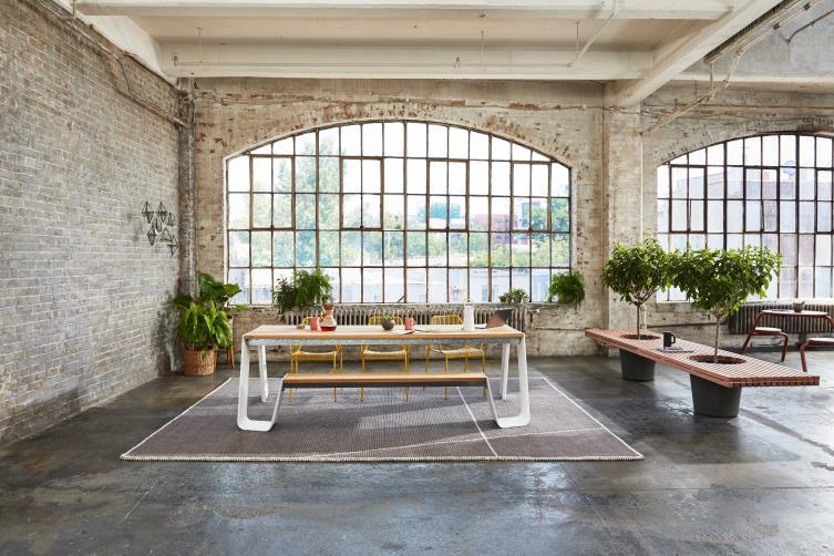 Cafetería de oficina con ventana en forma de arco, bancos de madera y plantas en maceta