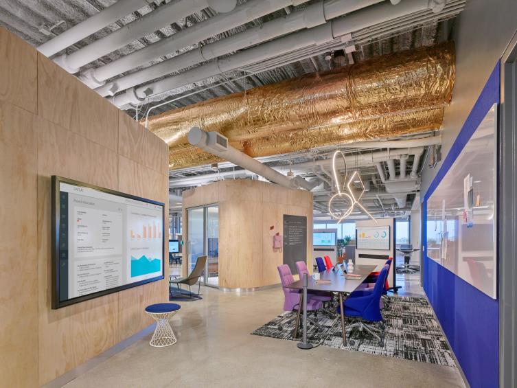 Vista del espacio compartido de la oficina con pizarra blanca magnética, mesa larga de sala de conferencias, asientos laterales y monitor en la pared